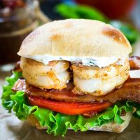 Front view of a sandwich filled with two grilled shrimp over bacon, tomato, and lettuce. The sandwich has a layer of aoili and the bread is a sliced Ciabatta roll.