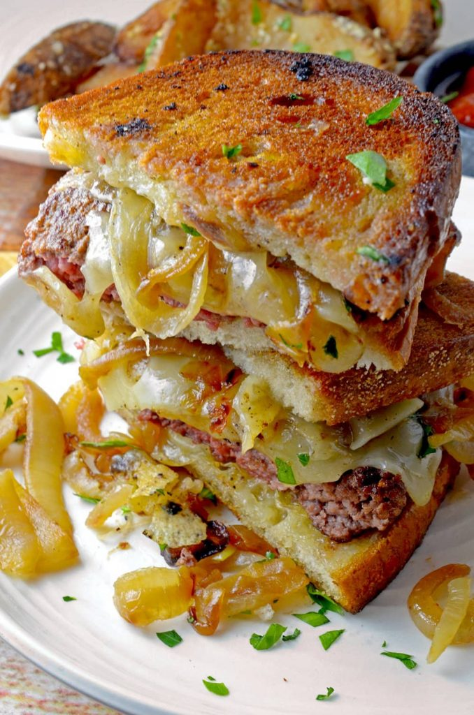 Stack of slices of a Patty Melt Sandwich on toasted bread showing the beef and onion ingredients.
