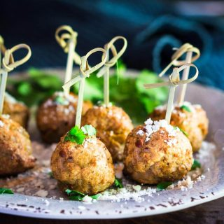 A table view of 6 meatballs with wooden skewers inserted through the top of each meatball sitting on a gray plate garnished with parsley and grated cheese in front of a blue napkin.