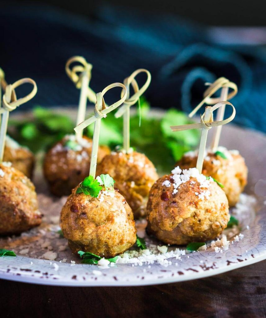 Tender delicious baked Turkey Meatballs with Green Chiles sitting on a plate with bamboo picks and dusted with cheese.