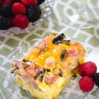 Top angled view of a piece of Ham and Cheese strata with melted cheese and mushrooms sitting on a clear glass plate over a green and white placemat. Fresh raspberries and blackberries sit next to it on the plate and a bowl of the berries sit in the background.