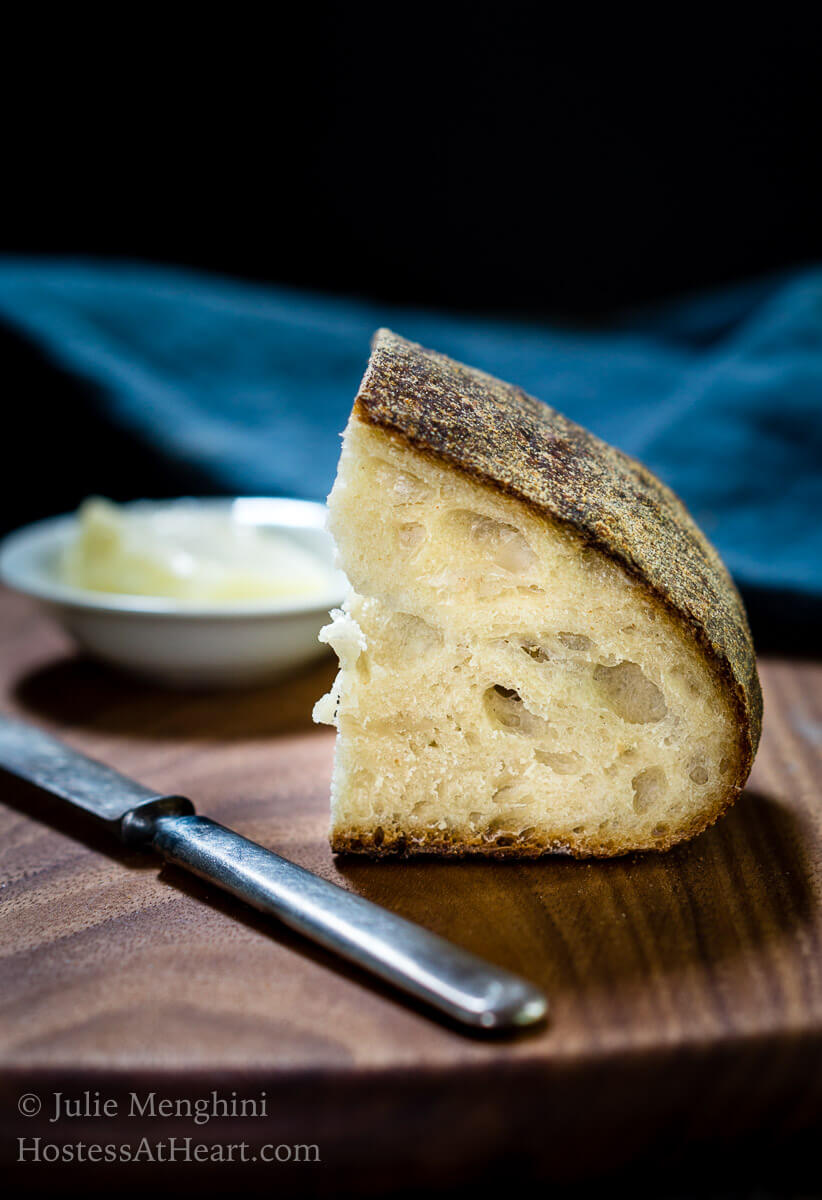 A small slice of sourdough bread sitting uprights showing the holes in the crumb over a wooden cutting bowl. A small knife and a white dish of butter sit next to the bread. A blue napkin sits in the background.