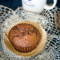 Chocolate banana muffin sitting in a parchment paper muffin paper over a clear plate. An espresso cup sits behind it.