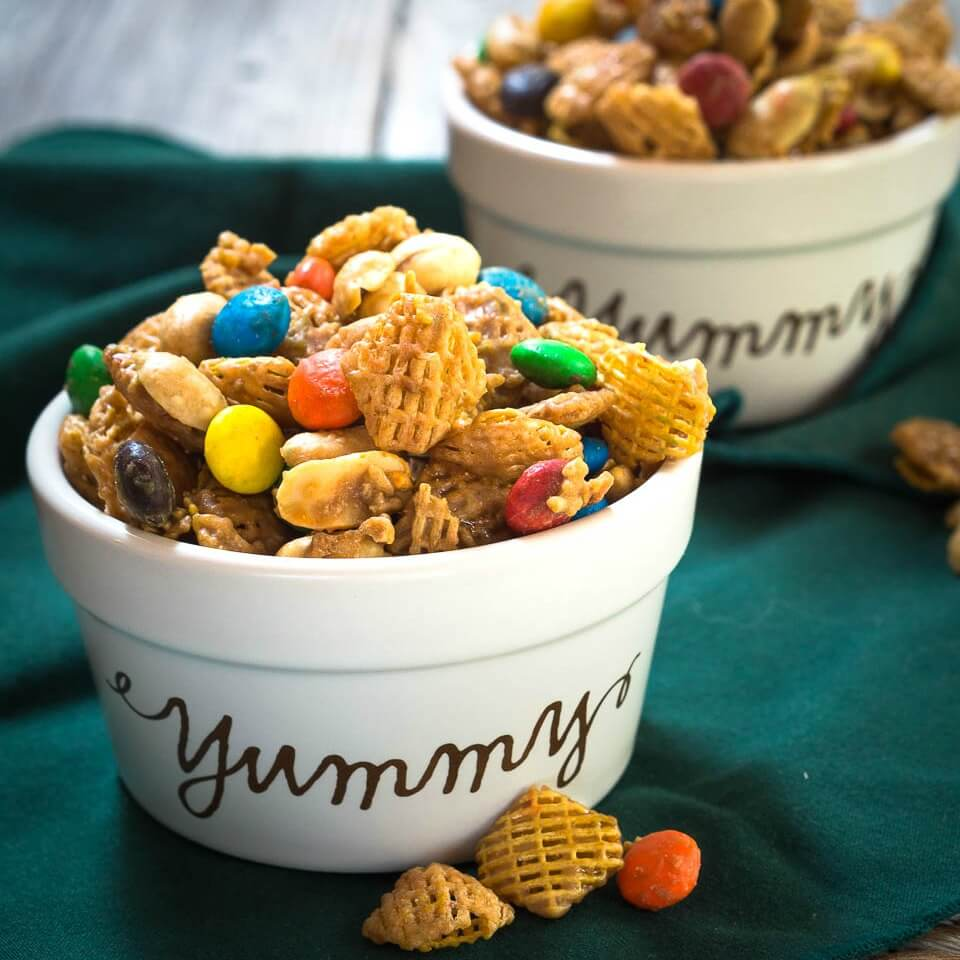 Two ramekins overflowing with an addictive Caramel Crispix Snack Mix which is loaded with sweet glazed cereal, peanuts and chocolate candies