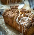 Loaf of Apple Pecan Streusel Pull Apart Bread with glaze drizzle