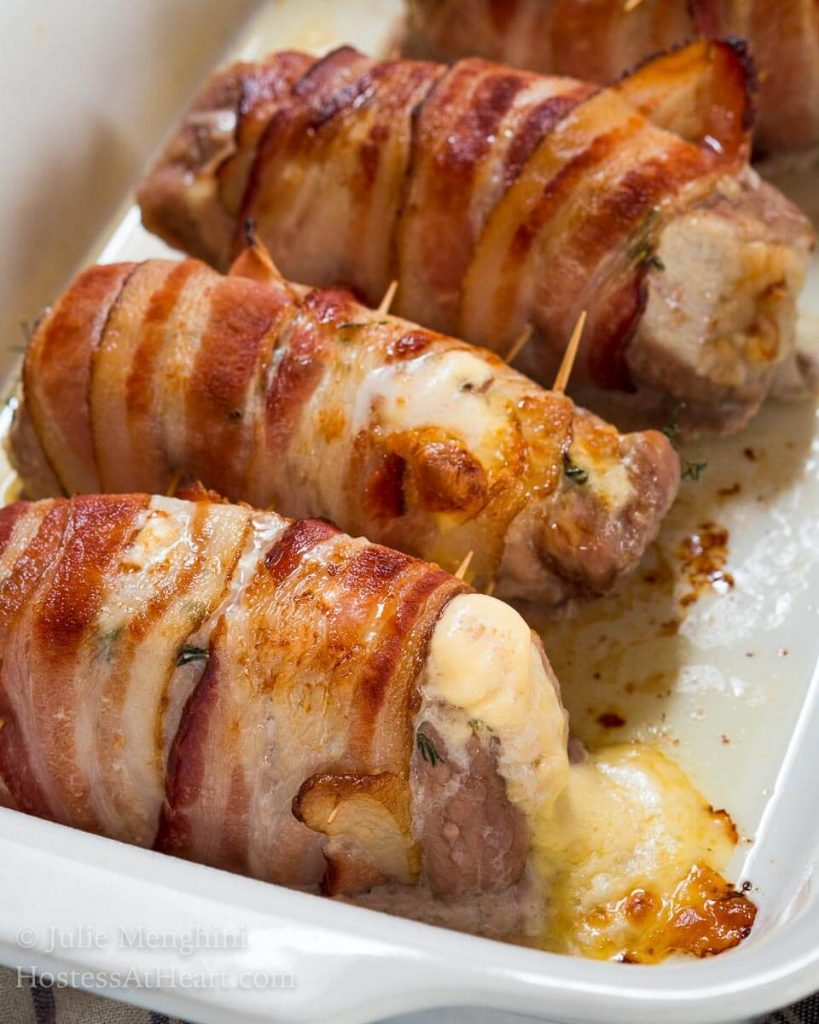 A baking dish holding three pork chop tenderloins wrapped in bacon that have cheese bubbling out of the ends.