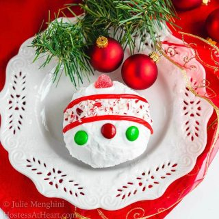A cake ball frosted in white frosting decorated with candy pieces to resemble a Christmas bulb on a white snowflake plate. A sprig of greenery and two red Christmas bulbs are at the top of the plate.