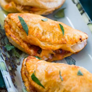 A close-up Cheese and Mushroom Empanadas sitting on a plate and garnished with fresh parsley.