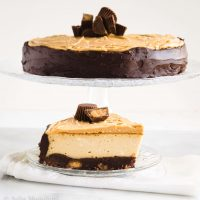 Side view of a cake stand holding a Cheesecake with a smooth chocolate edge and large shaved pieces of chocolate on the top. A slice of the cheesecake sits below it on a clear glass plate over a white napkin.