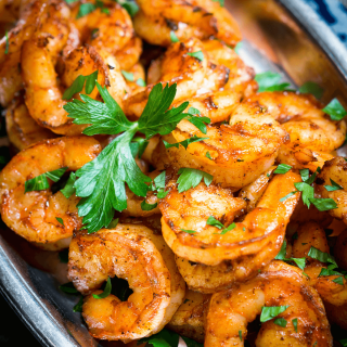 Close up top down view of shrimp seasoned in a red blackened seasoning and garnished with fresh parsley on a silver platter.
