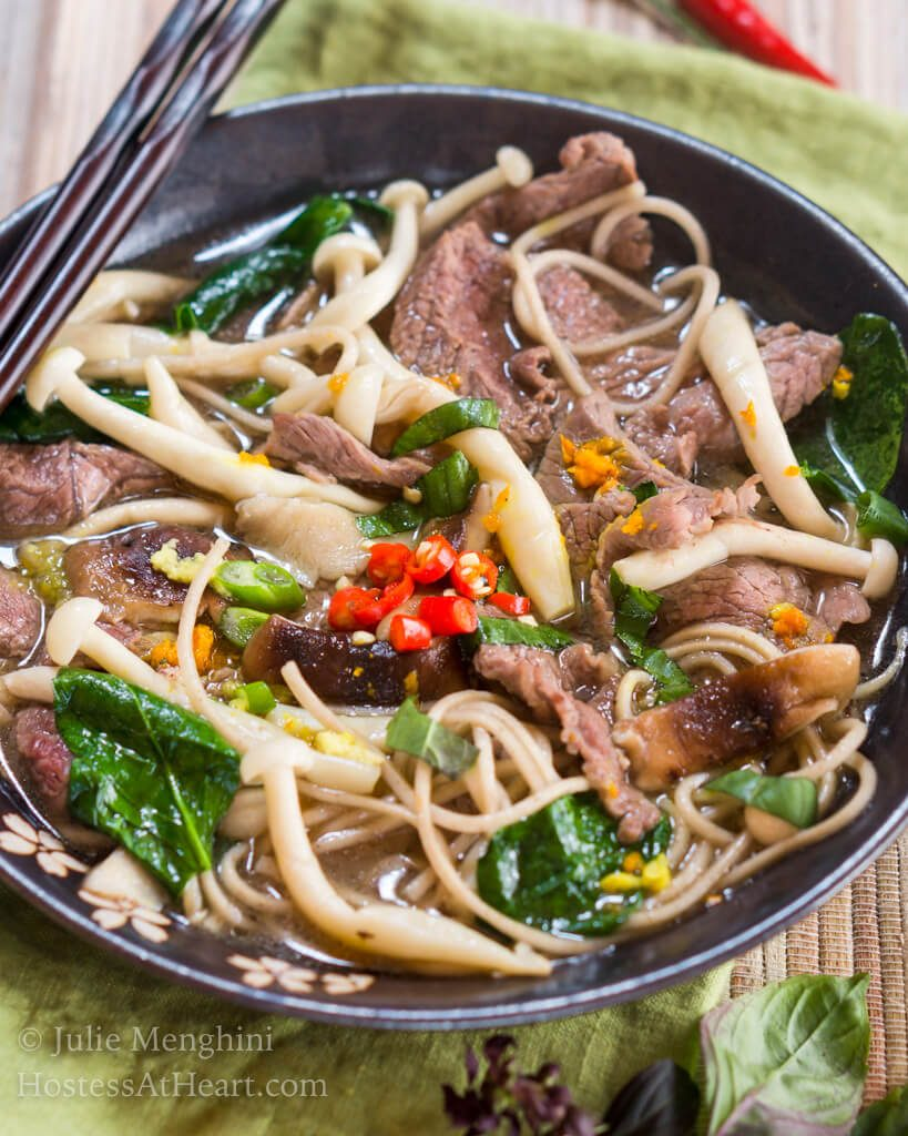 Top-down view of a dark gray bowl filled with thin slices of beef, mushrooms, buckwheat noodles, Thai basil and garnished with spicy red peppers. A set of chopsticks sits on the back of the bowl and Thai basil sits in front of the bowl.