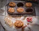 Rhubarb Oat Muffins in muffin tin and one muffin set in front with raw ingredients