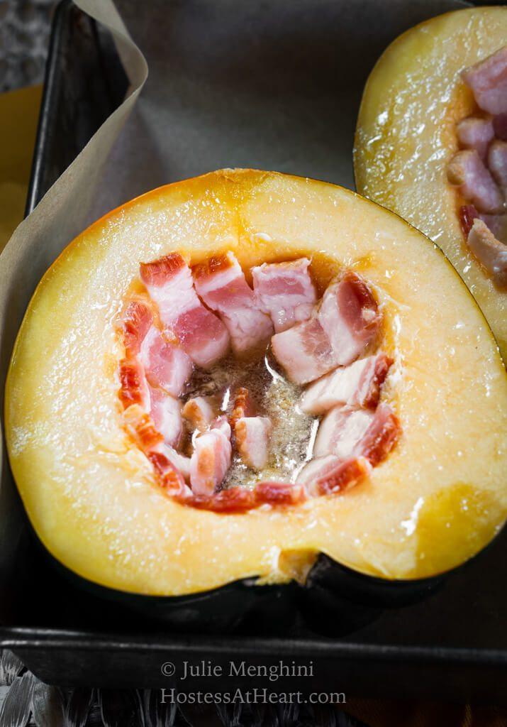 Raw half of an acorn squash stuffed with bacon