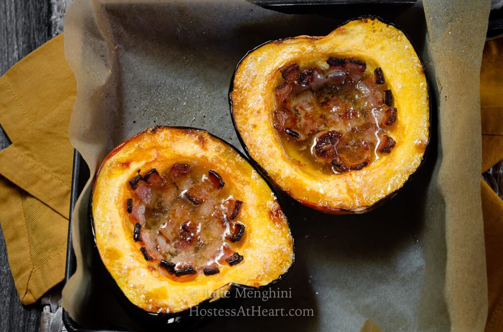 Side by side halves of baked acorn squash filled with bacon