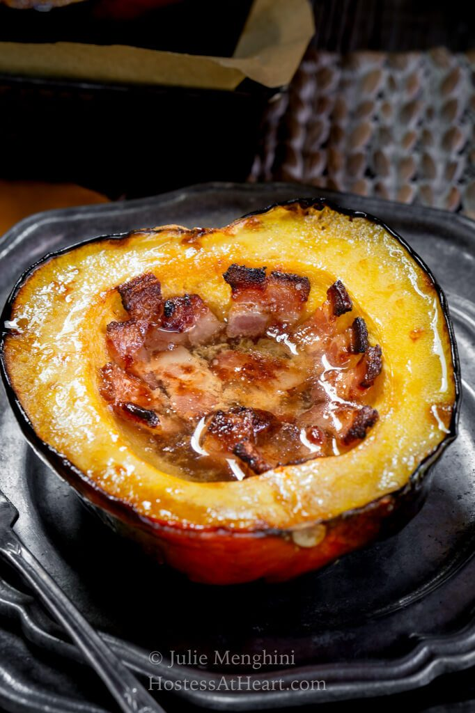 Acorn squash sliced in half and filled with bacon, butter and brown sugar on a metal plate
