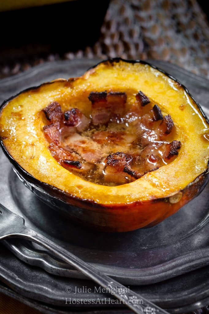 3/4 view of top side of a baked acorn squash filled with bacon