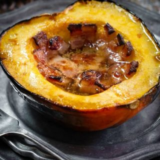 Half of a baked acorn squash filled with bacon