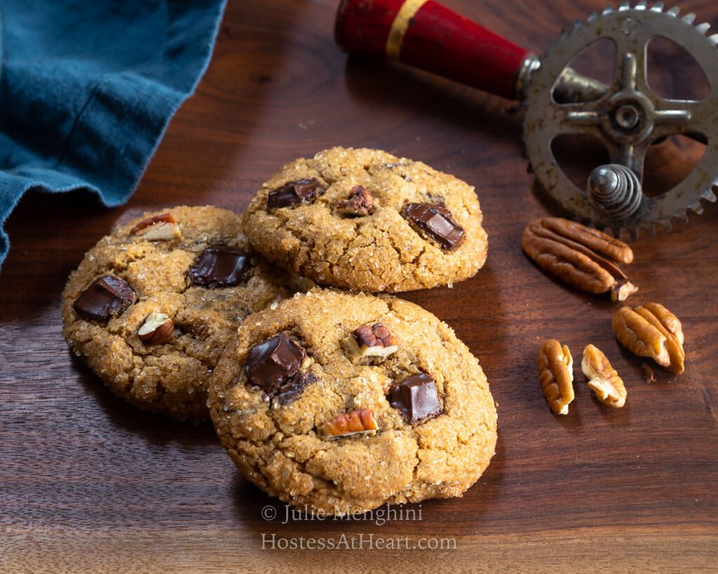 Three cookies in front of an antique egg beater.