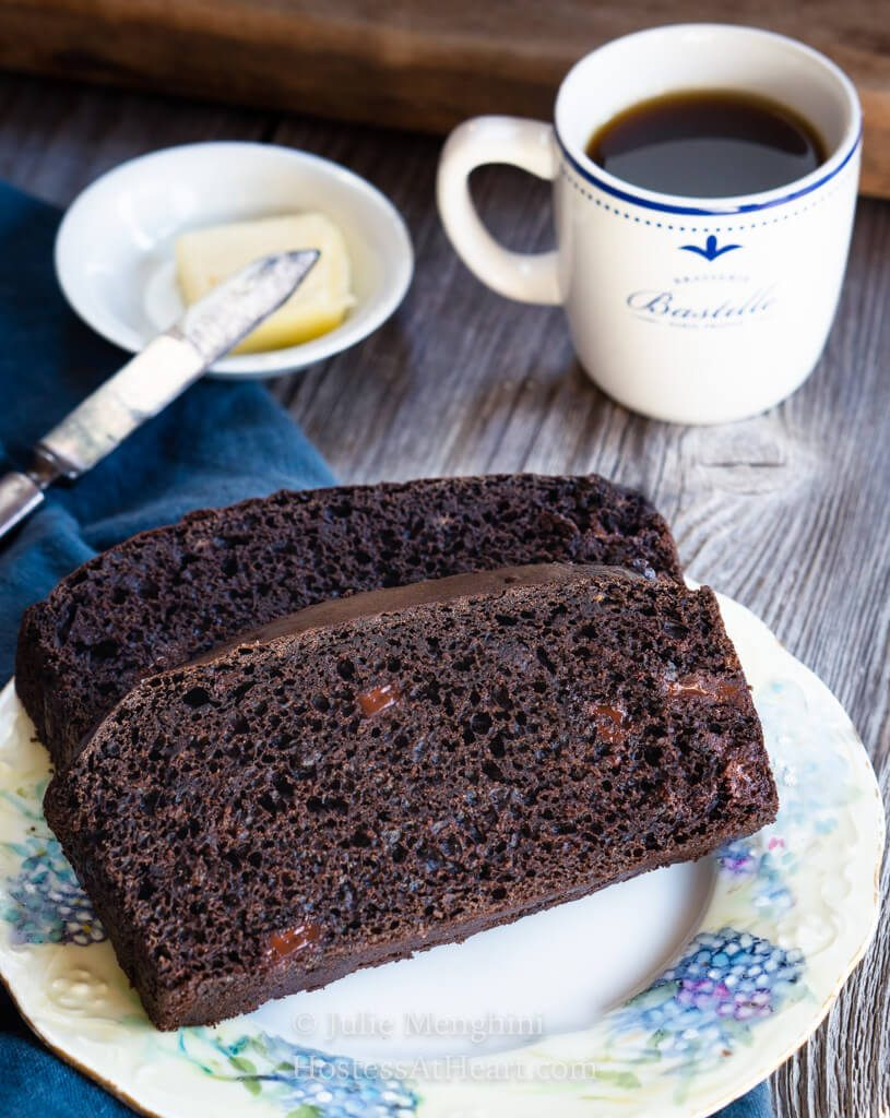 Two slices of chocolate banana bread showing melted chocolate chips in the crumb on a floral plate over a blue napkin. A cup of espresso sits behind it with a pad of butter in a small white dish with a knife next to it.