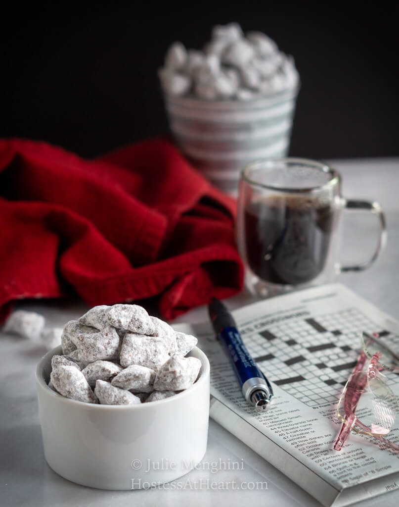 Close up with puppy chow in a bowl with a second serving in a pail