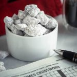A close up of a white ramekin filled with powdered sugar covered peanut butter pretzels. A crossword puzzle with a pen and a cup of coffee sit next to the bowl. A red napkin sits in the background.