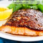 """A close up of a white plate holding a piece of baked Salmon with blackened seasoning and a drizzle of a brown butter lemon drizzle. Sliced lemon and a lettuce salad sit in the background.  The title """"Baked Blackened Salmon with Brown Butter Lemon Glaze"""" runs across the top."""
