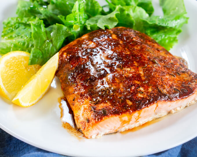 A close up of a baked filet of Salmon drizzled with brown butter and lemon juice sitting on a white plate. A lettuce salad and Lemon slices sit in the background.