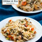 """A white plate of chicken and rice filled with carrots, onions, and herbs over a blue cloth. A second plate is in the background. The title """"Instant Pot Chicken and Rice appear in the top left corner."""