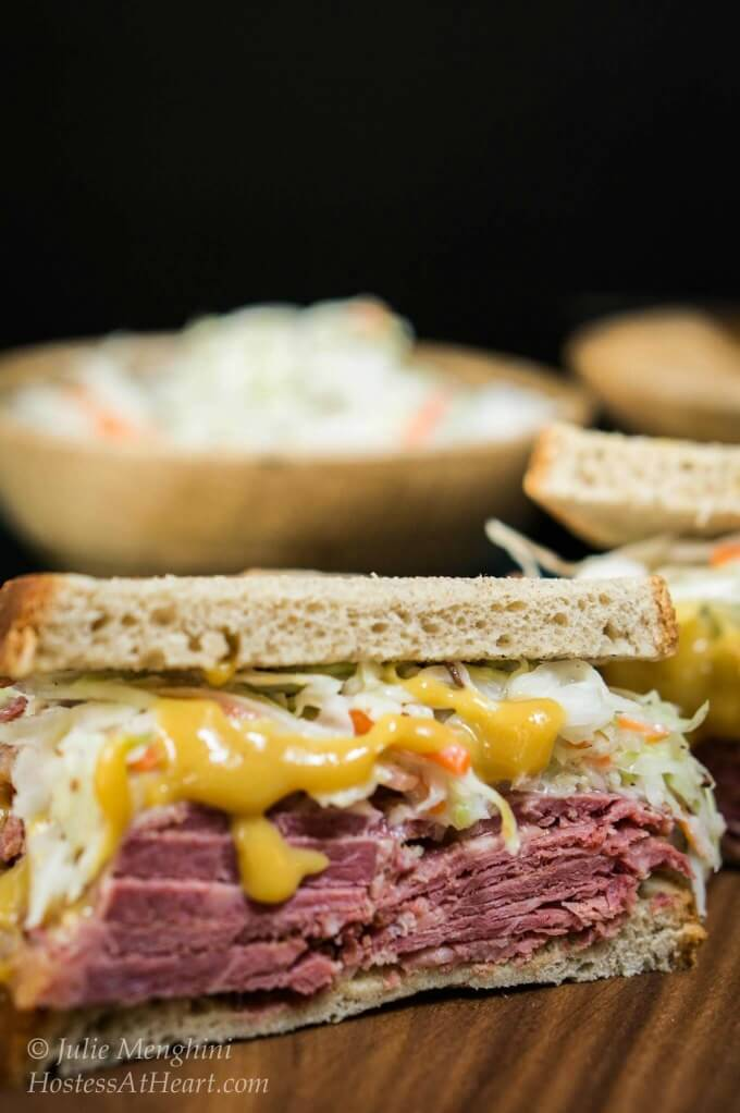 An amazing sandwich with heaps of stacked corned beef slathered in a brown sugar mustard and loaded with a caraway slaw that will have you craving this sandwich.