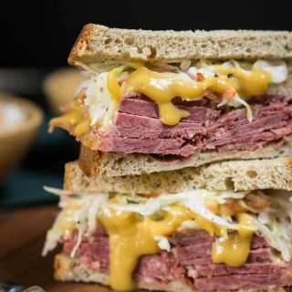 Double decker corned beef sandwich oozing with brown sugar mustard and heaped with a caraway slaw is a decadent mouthful.