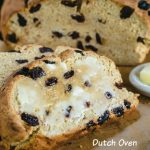 Level view of slices of soda bread dotted with raisins sitting on a wooden cutting bread. Butter is melting down the slice and a white bowl of butter sits to the side.