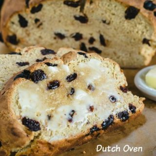 A slice of Dutch Oven Irish Soda Bread with Cherries and loaded with butter on a soft and tender crumb.