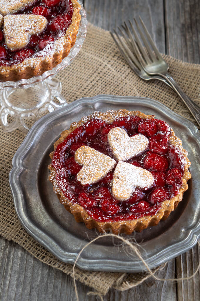 Mini cherry tortes full of bright red cherries are topped with heart-shaped cut out pastry