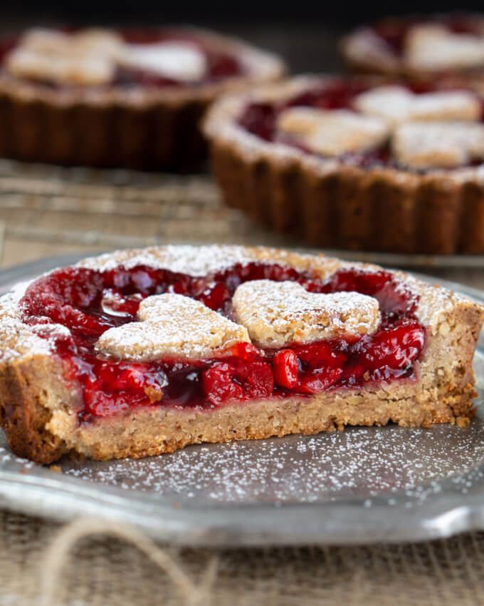 This sliced Sweet Cherry Torte shows a thick pecan shell holding a mound of bright red sweet cherries