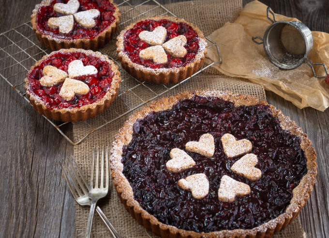 Fresh out of the oven is a whole sweet dark cherry torte and three mini tortes holding bright red cherries. All topped with cute heart cutouts of pecan shell