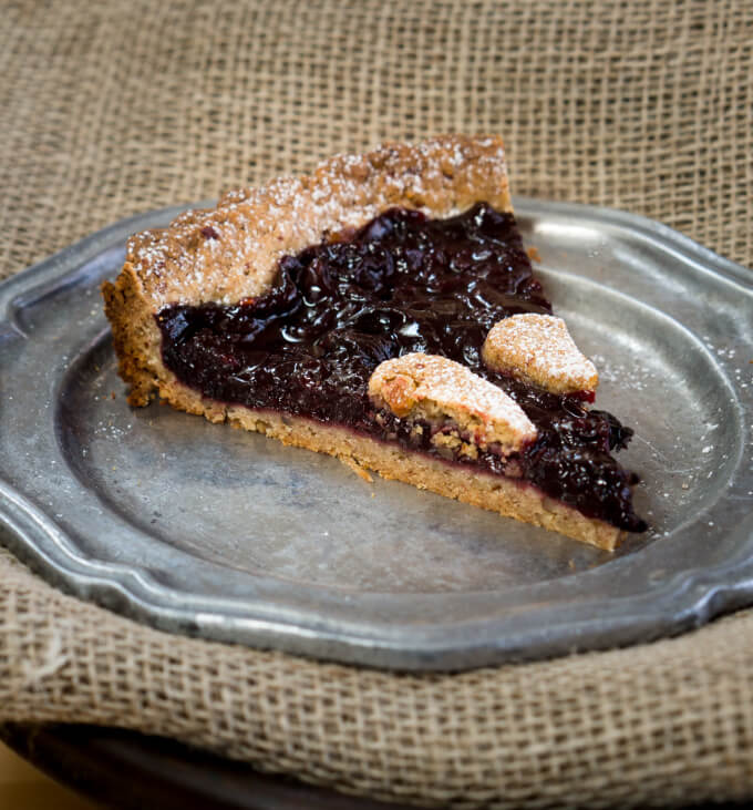 A slice of delicious sweet dark cherry torte dusted with powdered sugar