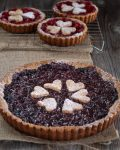 A beautiful dark sweet cherry torte with three bright red cherry mini tarts