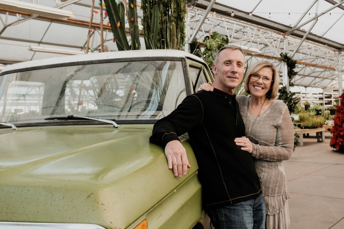 John and I posing in front of an antique green truck that was sitting in a garden nursery. Plants are in the background.