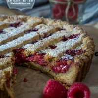 A tart with red raspberry filling and a lattice top dusted with powdered sugar with a piece missing Sitting on a piece of parchment paper. Fresh raspberries sit in the front and in a jar in the back.