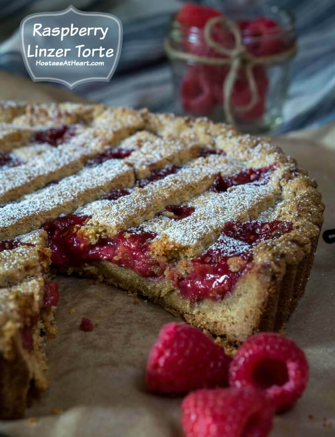 Raspberry Linzer Torte has a cookie like pecan shell and loaded with red raspberry filling under a lattice top and all dusted with powdered sugar
