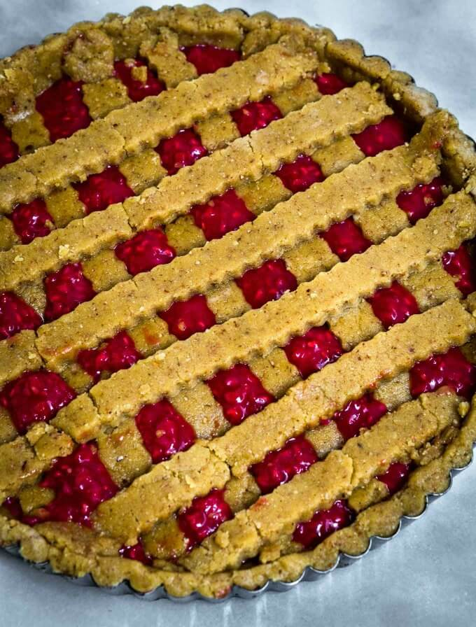 Assembled Raspberry Linzer Torte has a deep yellow color from fresh eggs and a bright red raspberry filling.