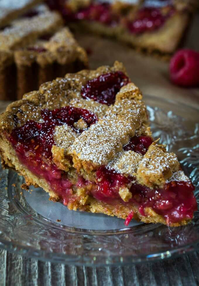 This slice of a Raspberry Linzer tort has a mound of sweet cherry filling nestled between an almond pastry shell.