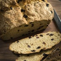 Top-down angled view of a loaf of soda bread dotted with raisins sitting on a wooden cutting bread. Two slices are cut from the front showing the inside of the loaf. a Butter knife sits beside the loaf.