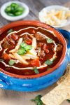 Chili Con Carne is a thick spicy stew loaded with meat and jalapenos. A pretty sour cream swirl and chopped cilantro mellows out the heat.