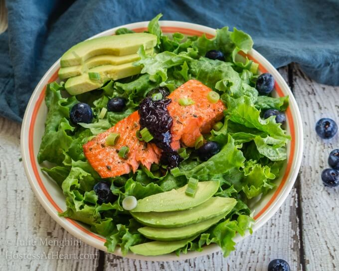 Superfood Salmon Salad with Balsamic Blueberry Sauce make the deep orange salmon the star on a bed of greens and topped with a delicious blueberry sauce