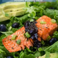 Green lettuce is adorned with a thick piece of salmon topped with a balsamic blueberry sauce. Sliced avocado sits in the background and the recipe title