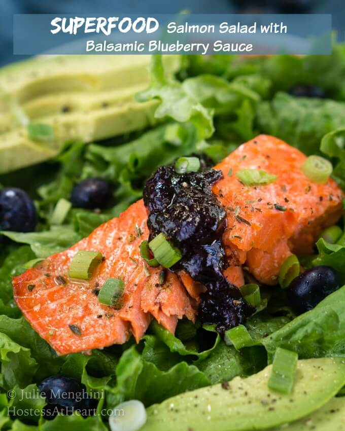 Glistening Superfood Salmon Salad with Balsamic Blueberry Sauce sitting on a bed of greens and surrounded by bright green avocado slices