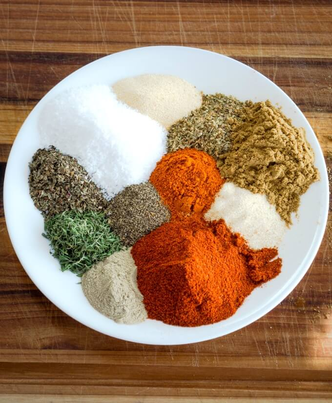 A white plate loaded with fresh spices and herbs that make a savory spicy Creole Seasoning blend.