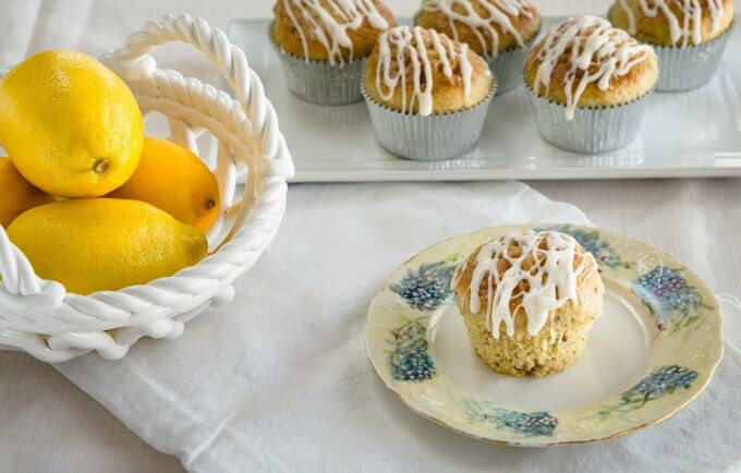 Whole lemon pistachio muffin drizzled with lemon glaze with a plate of muffins and a bowl of lemons in the background