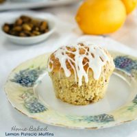 A Lemon Pistachio muffin drizzled with cream cheese glaze sits in the middle of a floral plate over a white tablecloth. A white dish of pistachios and two lemons sit in the background.